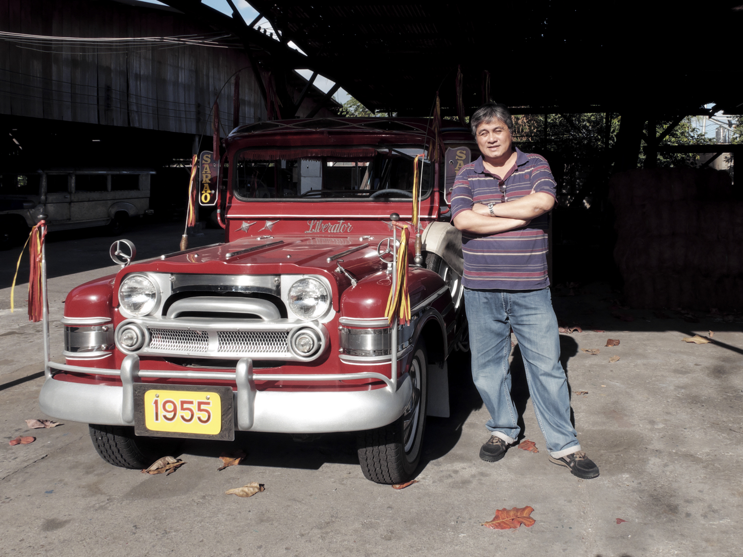 Mr. Edgardo Sarao poses beside a vintage 1955 Sarao Jeepney.